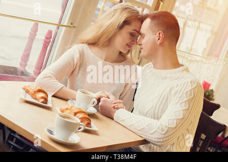 Young man and beautiful woman sitting close to each other and keeping their hands together while sitting in cozy cafe. Tender couple having romantic d - Stock Photo