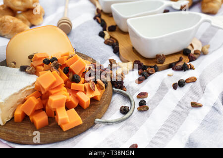 wooden tray with cheese assort layout on blue picnic blanket. healthy food weekends. - Stock Photo