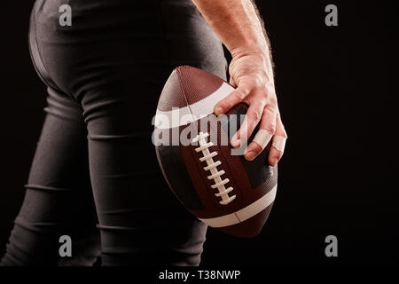 3D Cropped image of American football player holding ball against gloomy sky - Stock Photo