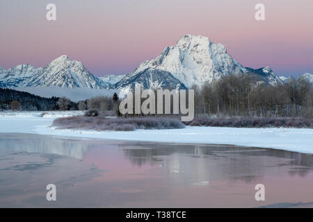 Mount Moran reflected in the icy waters of the Snake River as it winds through Oxbow Bend at sunrise. Grand Teton National Park, Wyoming - Stock Photo