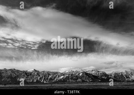 Light and feathery clouds passing above the Teton Mountains. Grand Teton National Park, Wyoming - Stock Photo