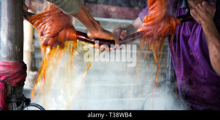 Traditional way of dying yarn in the traditional weaving village, Tangail district, Dhaka Division, Bangladesh - Stock Photo