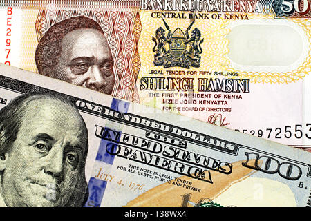 A close up image of a blue American one hundred dollar bill close up with a fifty Kenyan shilling bank note in macro - Stock Photo