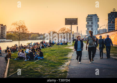 Berlin, Germany - april, 2019:  People at riverside at the Berlin Wall / East Side Gallery during sunset in Berlin, Germany - Stock Photo
