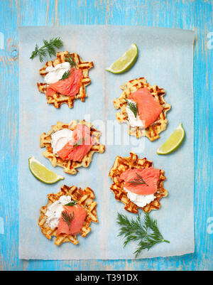 potato waffles with salmon, cream cheese on a blue wooden background. view from above - Stock Photo