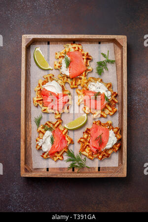 potato waffles with salmon, cream cheese on a wooden tray. view from above - Stock Photo