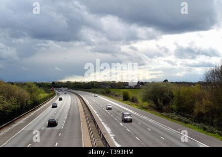 Elevated view of the M3 motorway with gathering storm clouds in the distance,  Shepperton Surrey England UK - Stock Photo