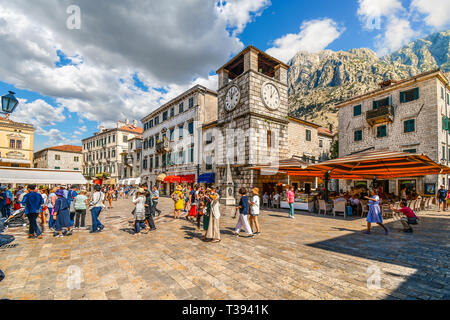 Tourists sightsee, dine at cafes and shop under the clock tower in the Square of the Arms, in the medieval walled city of Kotor, Montenegro - Stock Photo
