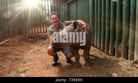 Young man with baby rhinoceros in South Africa - Stock Photo