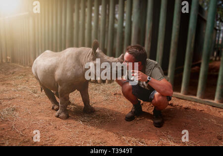 Young man kissing rhinoceros baby - Stock Photo