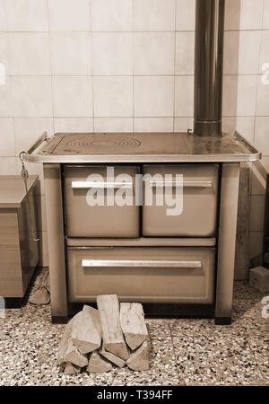 wood-burning stove in the kitchen of a chalet and the logs of wood with sepia toned effect - Stock Photo