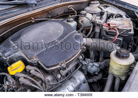 Old used petrol engine with rusty and dirty auto parts, dust accumulation and bad car maintenance. Dusty automobile components. View under the hood. - Stock Photo