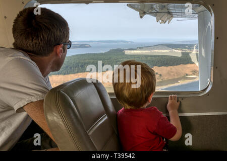 A father & son looking out of the window of a small float plane flying between Seattle and the San Juan Islands. - Stock Photo