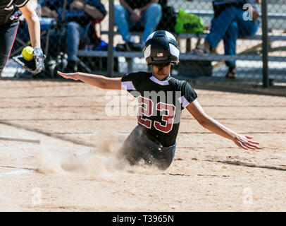 Female teenage softball player in black uniform sliding into home plate before the catcher can make the tag. - Stock Photo