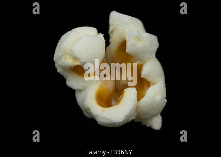 Macro image of a piece of popcorn isolated on a black background - Stock Photo