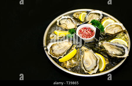 Fresh oysters on a plate with ice and lemon slices - Stock Photo