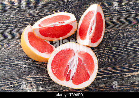 Tasty juicy red grapefruit on a wooden board, citrus fruits useful - Stock Photo