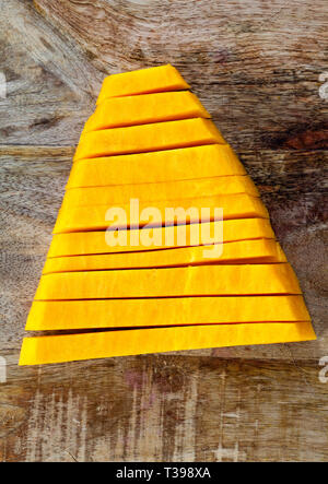 Sliced diced and other forms of ripe orange pumpkin during cooking and food, closeup in the kitchen - Stock Photo