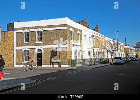 A woman riding a bike on Hargwyne Street and a row of terraced housing on Pulross Road in Brixton, South London SW9 England UK  KATHY DEWITT - Stock Photo