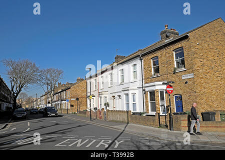 View of man walking and row of terraced housing on the corner of Dalyell Road and Pulross Rd in Brixton, South London England UK  KATHY DEWITT - Stock Photo