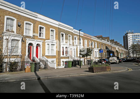 Row of terraced housing on Bellefirelds Road in Brixton with parked cars and rubbish bins outside houses, South London England UK  KATHY DEWITT - Stock Photo