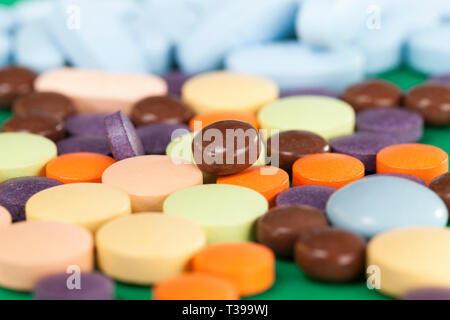 Multi-colored pills on a green background of various packs, a bunch of drugs on paper, medical treatment help, closeup - Stock Photo