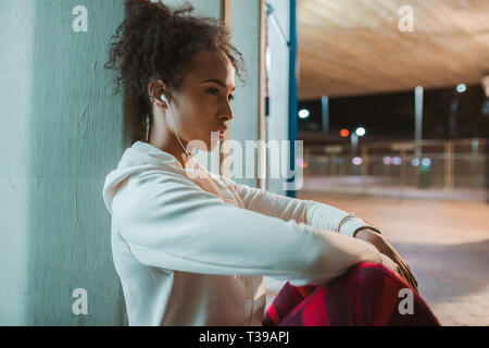 Side view of young woman sitting under a bridge and taking rest after running exercise. Urban runner resting after training in the night. - Stock Photo