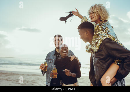 Group of multi-ethnic friends enjoying their holidays on the beach. Two cheerful couples on summer vacation. - Stock Photo