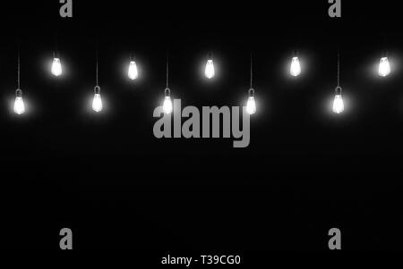 Hanging light bulbs on black background with copy space, black and white photography - Stock Photo