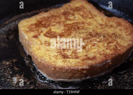 Making breakfast French toast in cast iron frying pan. - Stock Photo