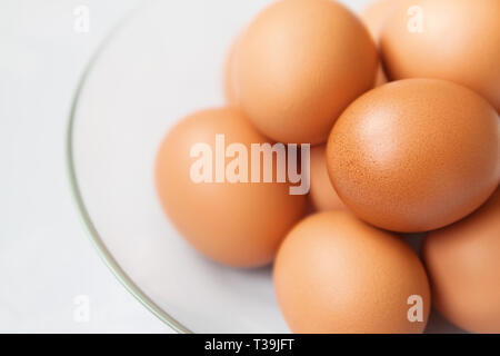 Fresh brown hen's eggs in the glass plate close up - Stock Photo