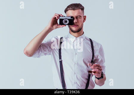 Handsome and stylish man in white shirt and suspenders making photo on old vintage camera and holding glass of whiskey in hand while standing against  - Stock Photo