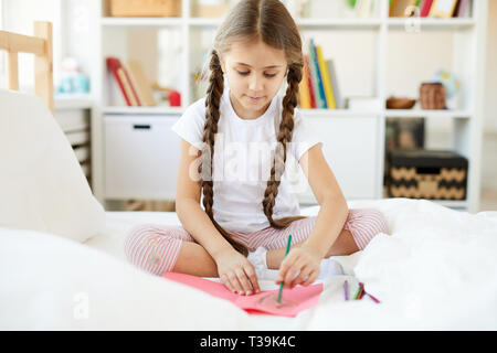 Girl Drawing Pictures on Bed