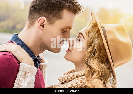 Totally in love. Cropped image of young beautiful couple keeping eyes closed while standing close face to face. Young couple in love walking outdoors. - Stock Photo