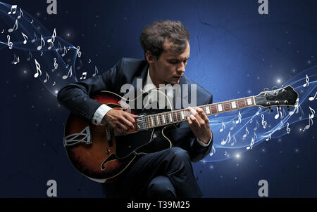Lonely musical composer with guitar and sparkling musical notes around - Stock Photo