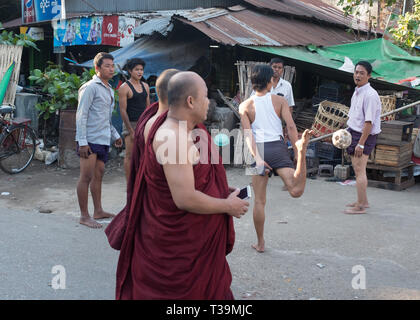 Two monks walking past men playing Chinlone also known as caneball, is the traditional, national sport of Myanmar (Burma). It is non-competitive, with - Stock Photo