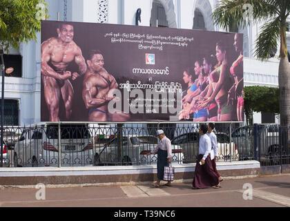 Men walking past a billboard advertising body building on Sule Pagoda Roundabout in Yangon (Rangoon), Myanmar (Burma) - Stock Photo