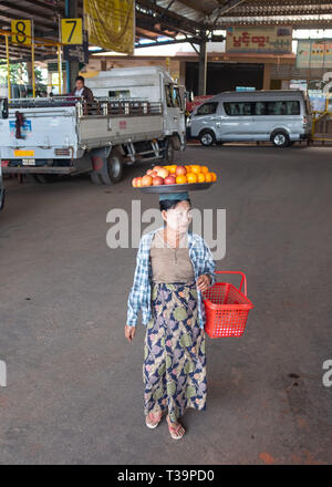Burmese woman with thanaka face painting carrying a plate with fruit on  head at bus station in Kinpun Vlllage,Kyaiktiyo,Myanmar. - Stock Photo