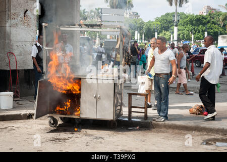 HAVANA CUBA - JULY 7 2012; Food trolley catches fire in city street whiole people staround watching. - Stock Photo