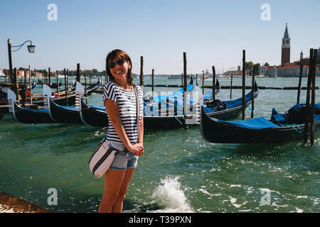 Young woman tourist standing in front of the gondolas at Traghetto molo near to the San Marco Square in Venice, Italy. Travel concept. - Stock Photo