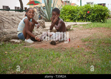 HAVANA CUBA - JULY 7 2012; Two children playing beside street with old cans for makesift toys from poor community but happy - Stock Photo