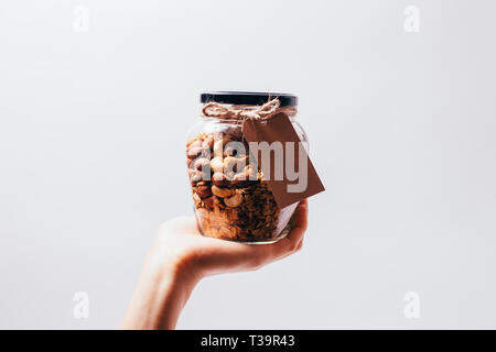 Woman's hand holding homemade granola. Glass jar full of baked oatmeal cereal with nuts on white background. - Stock Photo