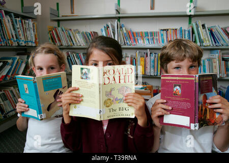 primary,school,pupils,kids,girl,boy,read,library,junior,Roald Dahl,The BFG, children's,book,books,peering,over,book,books,southern,England, - Stock Photo