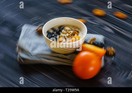 Blur in Motion Abstract Background of the Oatmeal with Persimmon, Prune, Dried Apricots, Walnut and Sesame on a Black Wooden Table. - Stock Photo