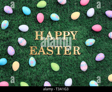 Gold Happy Easter text surrounded with colorful Easter eggs on grass - Stock Photo