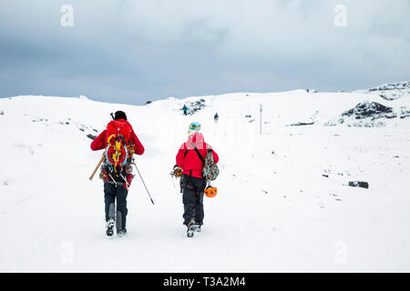 Two climbers hikers walking in the snow near Solheimajokull Glacier, Iceland - Stock Photo