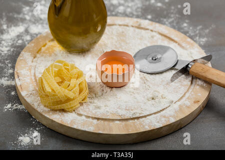 Fresh homemade pasta tagliatelle made with flour, eggs and water. Italian cuisine concept. - Stock Photo