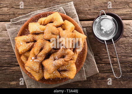 Traditional Chilean sweet calzones rotos deep-fried pastries sprinkled with powdered sugar served on wooden plate, photographed overhead - Stock Photo