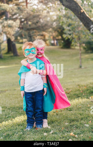 Cute adorable preschool Caucasian children boy and girl playing superheroes. Two kids friends hugging together outdoors in park. Happy active childhoo - Stock Photo
