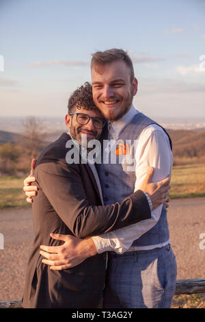 two man, smiling and happy gay couple hugging outdoors in nature. - Stock Photo